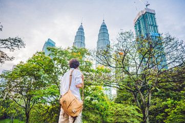 Man tourist in Malaysia looks at the Petronas Twin Towers