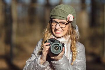 Young european woman photographer enjoying first spring sun exploring suburban locations
