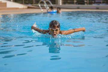 Swimming child boy butterfly style with gogles
