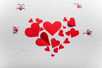 Wooden white background with red hearts. The concept of Valentin