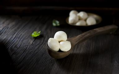 mini mozzarella and basil on a wooden background
