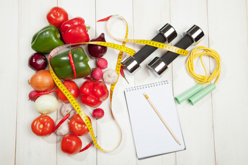 Sport and diet. Healthy lifestyle. Vegetables, dumbbells  notebook. Peppers, tomatoes, garlic, onions  radishes on a white background