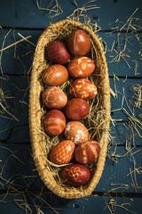 Ostereier (gefärbt mit Zwiebelschalen) in einem Nest auf blauen Holztisch