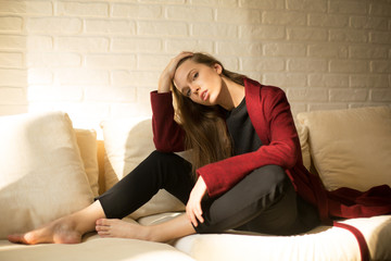 gorgeous girl in a red coat sitting on the couch