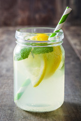 Lemonade drink in a jar glass on wooden background. Copyspace.