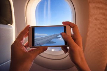 Young woman take photo on mobile phone from airplane