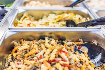 Macro closeup of different pasta salads in salad bar counter