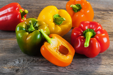 Fresh colored bell pepper on wooden background