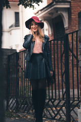 Beautiful blonde girl with red hat and lips looking tenderly with inviting eyes. Trendy dressed girl posing near black iron fence, wearing black skirt, black jacket and red floppy hat.