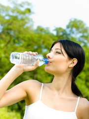 woman drinking water at workout, outdoors