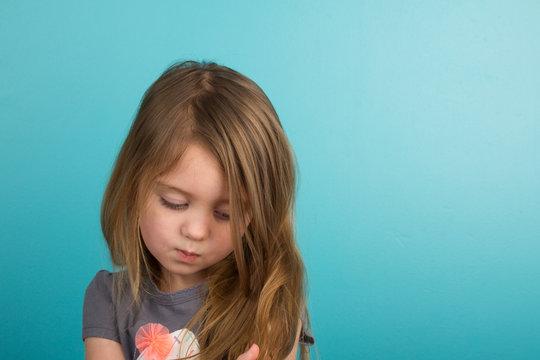 Sad little girl against teal background
