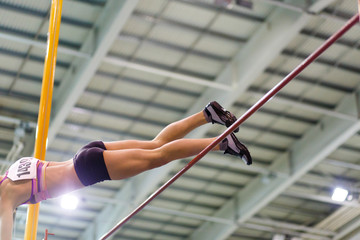 Young athletic woman vaoulting over bar with pole against flag on indoor track and field championship