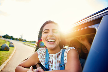 Pretty woman in speeding car smiles at camera
