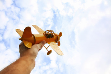 close up photo of man's hand holding toy airplane