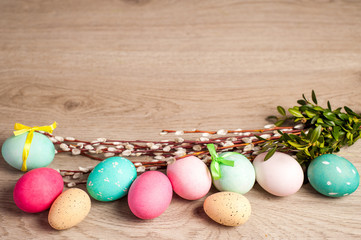 Easter composition of the branches, cakes, tulips colored eggs cooked for the holiday on the wooden background with free space for an inscription