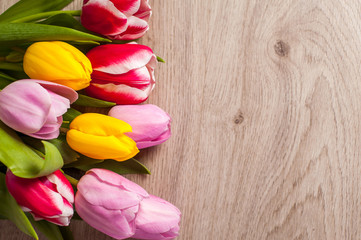 The composition of tulips of different colors on a wooden background, greeting card with free place for inscriptions on any holiday