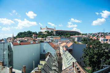 Panoramic view of Bratislava, a capital of Slovakia, old houses with tile roofs and a castle - a symbol of the city.