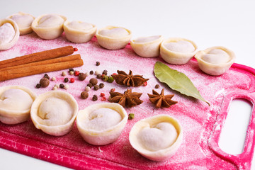 Dumplings home cooking in a bright pink board with flour and seasonings. Colorful board with dumplings, spice - cinnamon sticks, anise and pepper, food, white background
