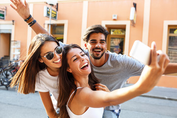 Group of happy young friends having fun on city street.Taking selfie.