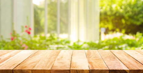 Empty wood table top on blur abstract green from garden and house in morning background.For montage product display or  key visual layout