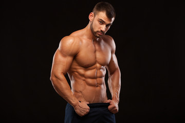 Strong Athletic Man - Fitness Model showing Torso with six pack abs. stands straight and puts his hands in trousers. isolated on black background with copyspace.