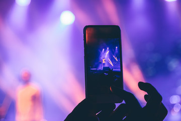 Woman takes pictures on the phone at a concert