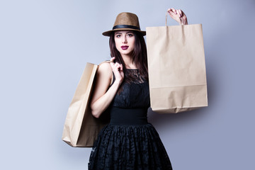 beautiful young woman with shoping bags standing in front of wonderful white studio background