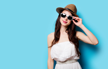 beautiful young woman in sunglasses standing in front of wonderful blue background