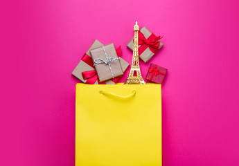 cute gifts and beautiful eiffel tower shaped toy in shopping bag on wonderful pink background