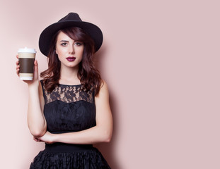 beautiful young woman with cup of coffee on the wonderful pink background