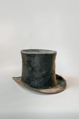 Worn vintage black top hat isolated against white background