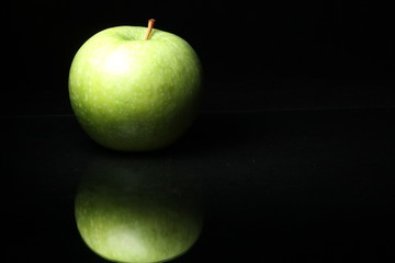 close up of one fresh green apple on a dark black background with reflection isolated