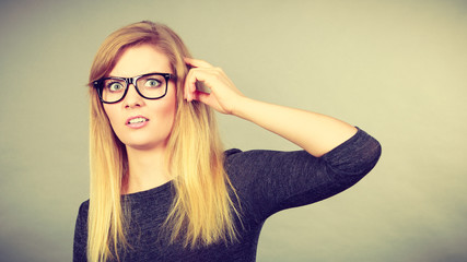Nerdy woman in eyeglasses being confused