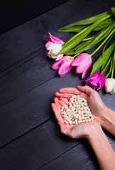 Bouquet of tender pink tulips and hands holding pearl necklace on black wooden background