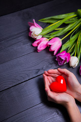 Bouquet of tender pink tulips and hands holding red heart on black wooden background
