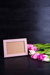 Bouquet of tender pink tulips and empty photo frame on black wooden background