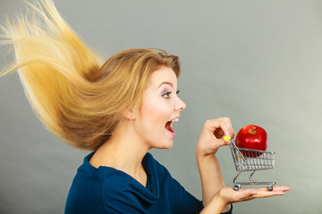 Woman holding shopping cart with apple inside