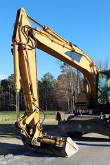 A yellow excavator on road construction