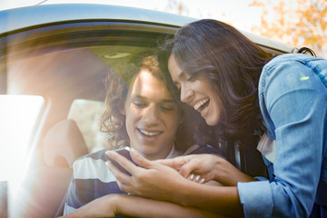 Couple looking for directions on smartphone before embarking on road trip