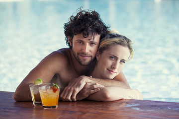 Couple relaxing together in pool with cocktails