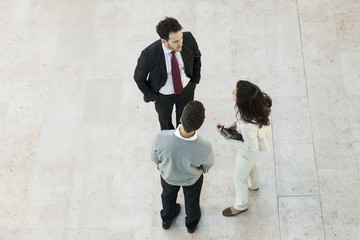 Business manager talking to associates in office lobby