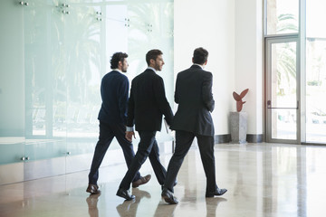 Business people walking together in office corridor