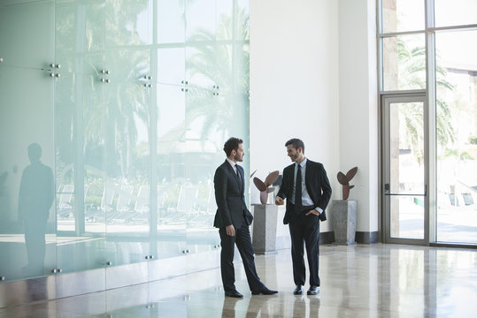 Business associates talking in office lobby