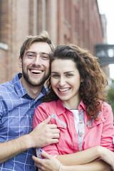 Affectionate couple smiling outdoors, portrait