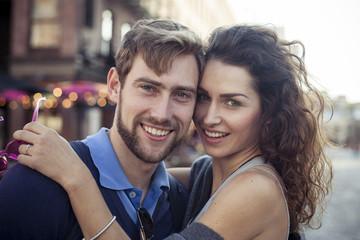 Couple embracing outdoors, portrait