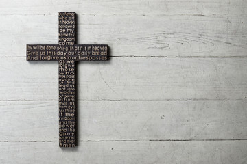 Dark wooden cross with carved the Lord's Prayer on worn white wooden background