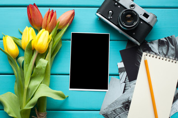 Tulips, vintage retro camera and Notepad with pencil, and finished photos on a blue wooden background