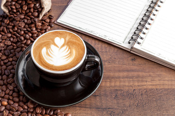 Wall Mural - Coffee cup of latte art in the black color cup with some coffee beans and notebook on wooden background with copy space