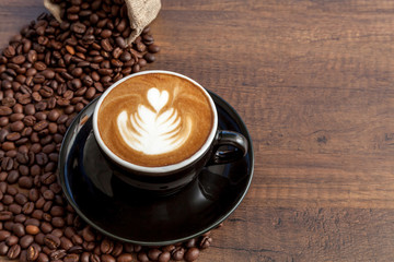 Wall Mural - Coffee cup of latte art in the black color cup with some coffee beans on wooden background