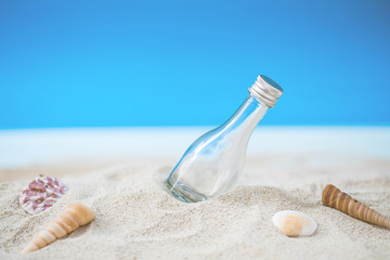 bottle over tropical sand beach with clear blue sky, background for love travel on vacation summer concept.
